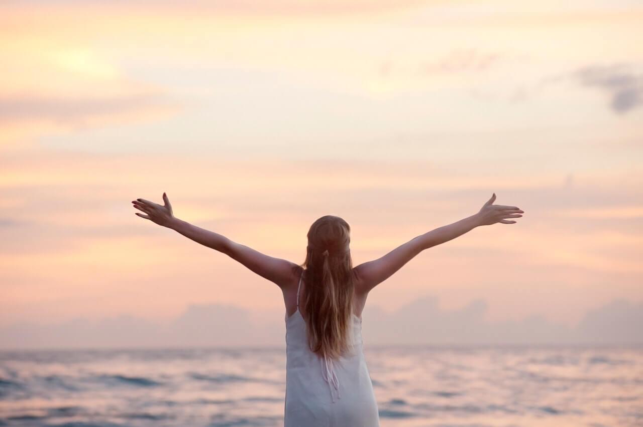 imagem de uma mulher de braços abertos olhando para o mar