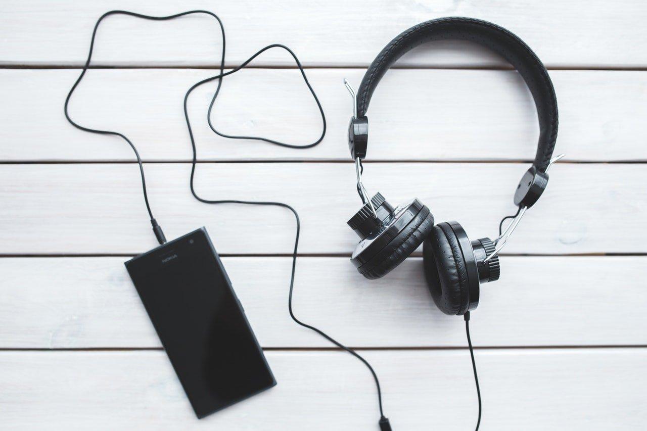 fone de ouvido e celular em uma superficie branca