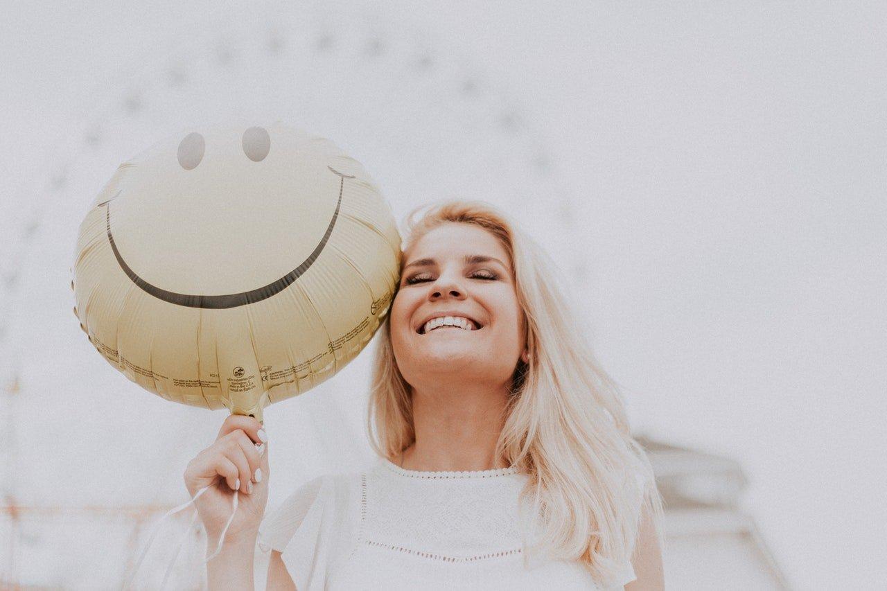 mulher feliz segura um balão de emoticon feliz em um parque