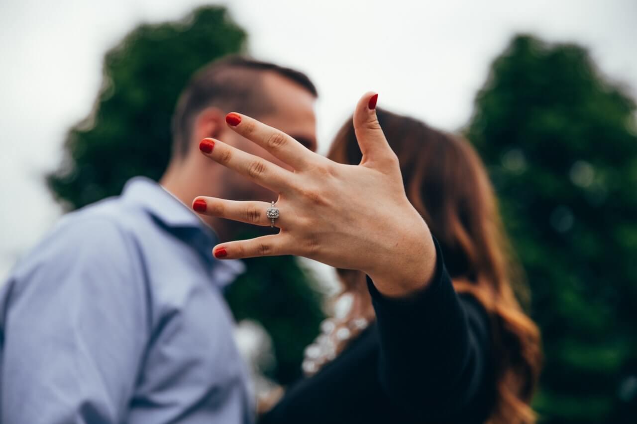 casal se beija e mulher exibe se anel de noivado