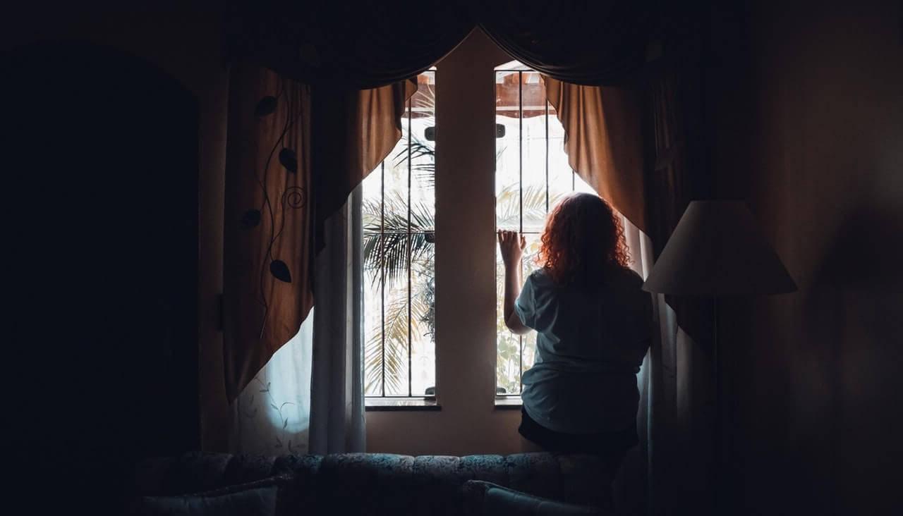 mulher olhando pela janela no isolamento social