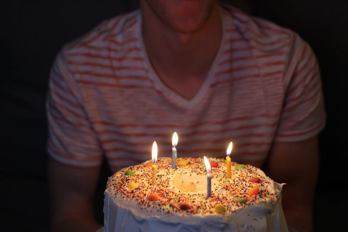 bolo de aniversário com velas e homem ao fundo ilustrando a matéria de presente de aniversario para namorado