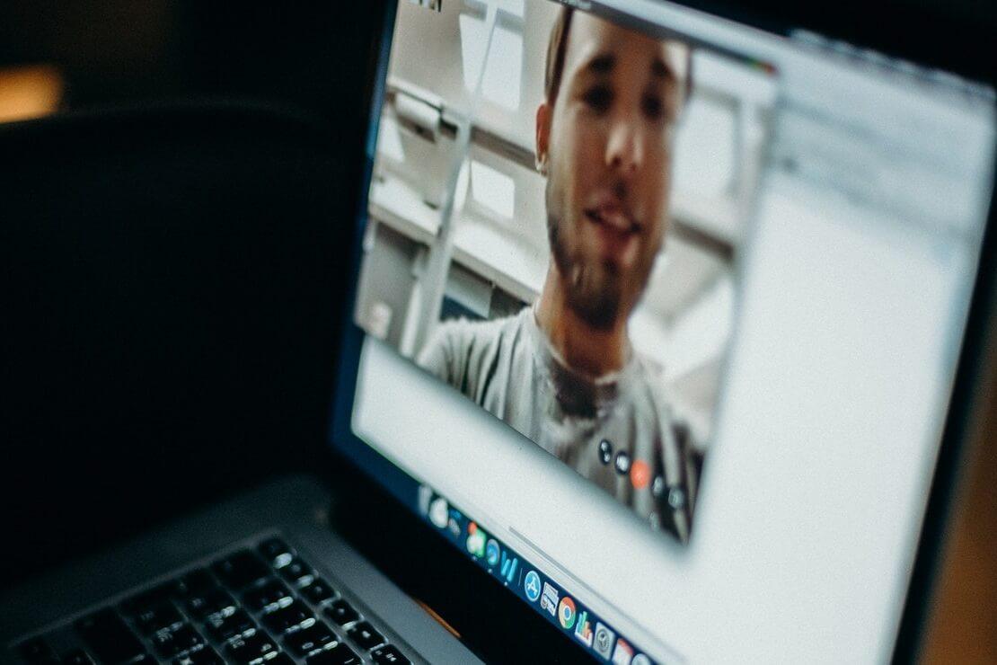 homem aparece em videochamada em notebook, ilustrando um namoro à distância