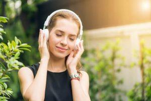 mulher escuta com rosto relaxado música com mensagem de positividade