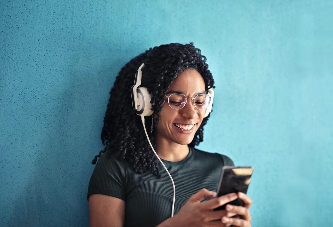 para frases de músicas, moça escuta de fone música no celular