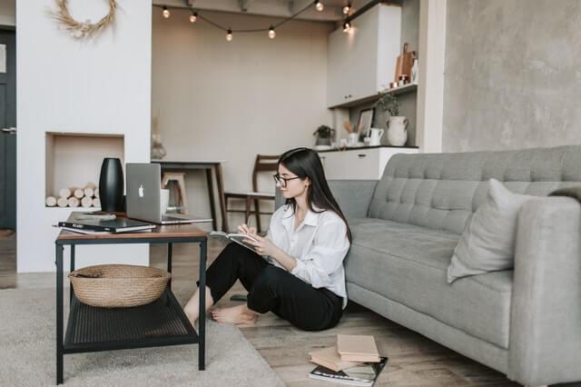 mulher lê livro sozinha em sala