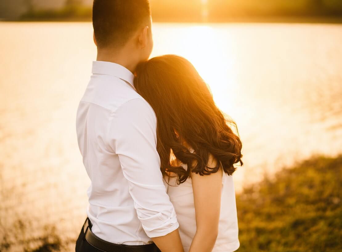 presente romântico para namorada representado por casal abraçado admirando o pôr do sol