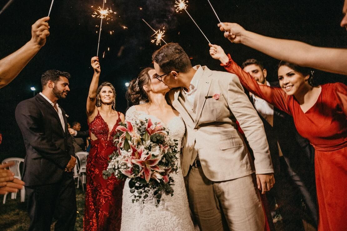 casal se beija na saída da igreja ao lado dos padrinhos, ilustrando presente para padrinhos de casamento