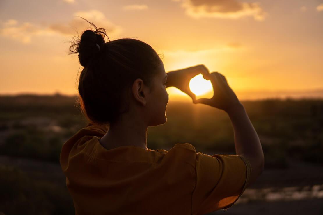 se auto presentear é um ato de amor - menina faz coração com as mãos, voltada ao pôr do sol