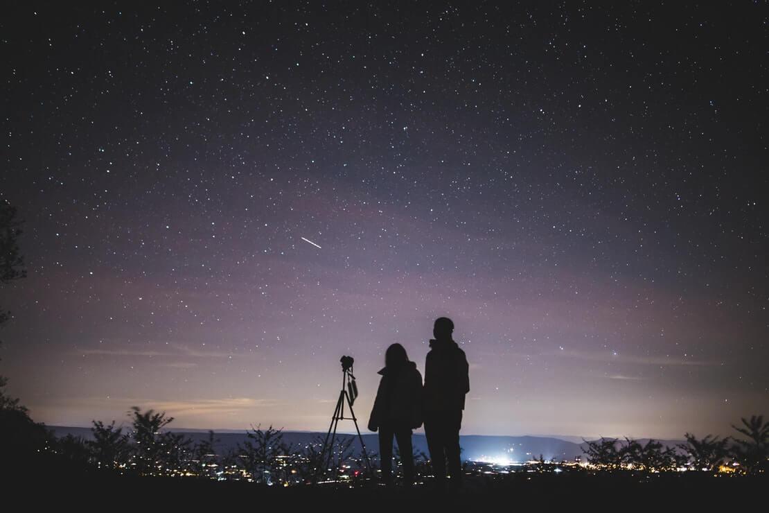 Calendário astronômico 2021 - casal observa o céu estrelado ao lado de um telescópio