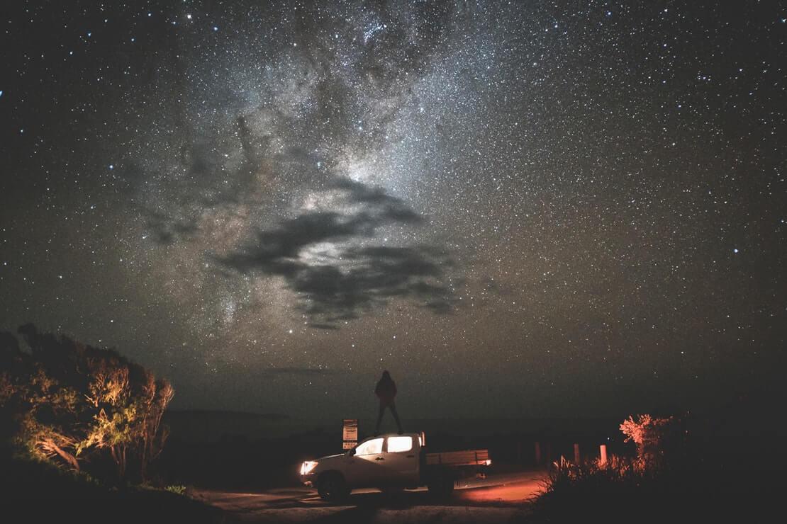 como estava o céu em um dia especial - homem observa em cima de um carro céu noturno